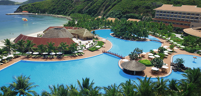 A thatched roofed holiday resort set around a huge pool; on the coast; near forested mountains