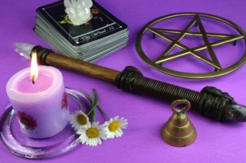 Magic tools: a pink candle, wooden and crystal wand, pentagram, tarot cards, crystal and a bell on a purple background.