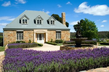A pretty stone cottage set amidst lavender with a fountain out the front