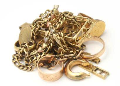A pile of gold jewellery on a white background