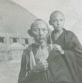 A black and white photograph depicting two Buddhist monks outside a straw building