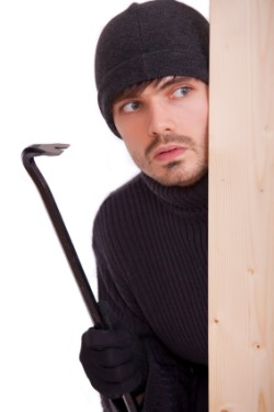 A robber with a crowbar hiding behind a door