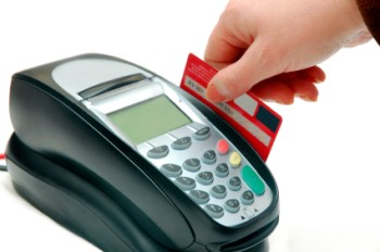 A hand swiping a credit card though an eftpos machine