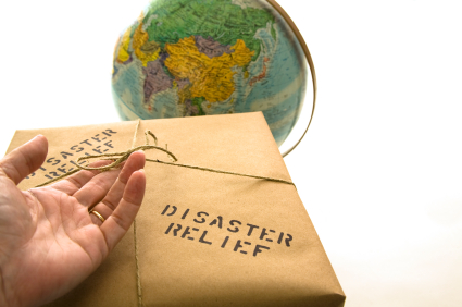 Hand holding brown paper parcel, with the words disaster relief written on it in front of a globe.